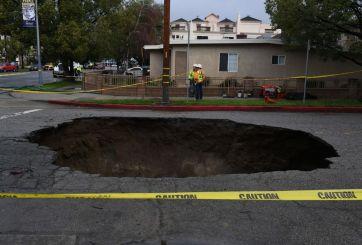 Rescatan a mujer cuyo carro cayó en agujero en LA