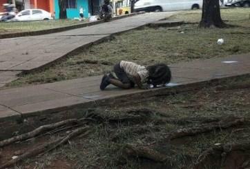 Foto de una niña intentando tomar agua del suelo impacta