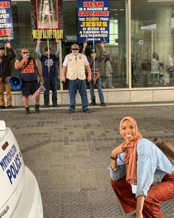 Mujer musulmana posa feliz ante manifestantes y se vuelve viral