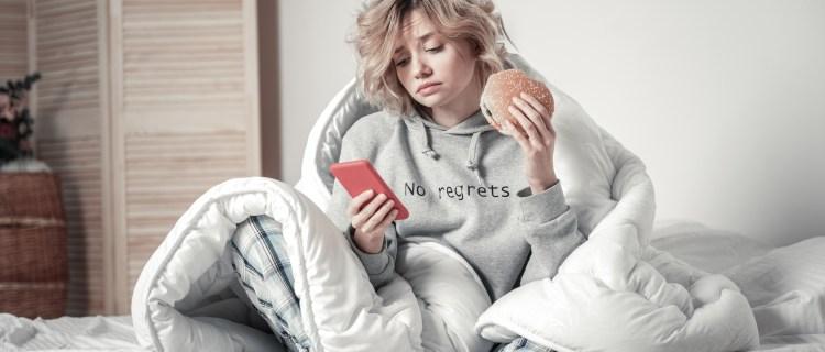 mujer triste comiendo hamburguesa