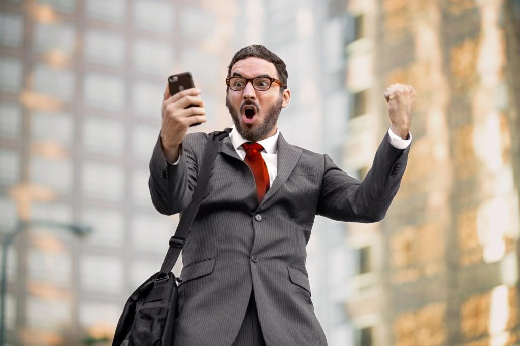 hombre viendo su celular y festejando