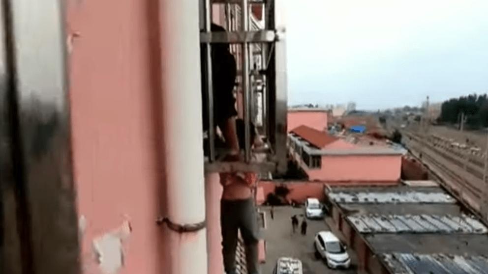 niño colgando de balcón