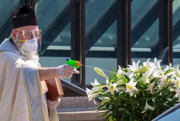 Con pistola de agua un sacerdote bendijo a sus feligreses a distancia