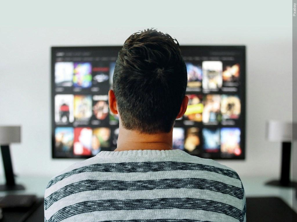 Joven decidiedo que ver en plataforma de streaming