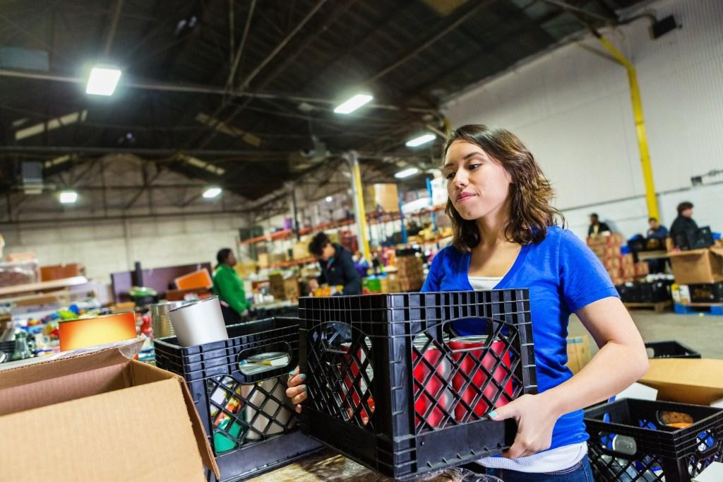 Joven sirve de voluntaria en banco de alimentos